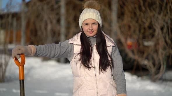 Thumbnail for Junges Mädchen steht mit einer Schaufel im Hinterhof. Frau bereit, Schnee nach Schneefall zu löschen