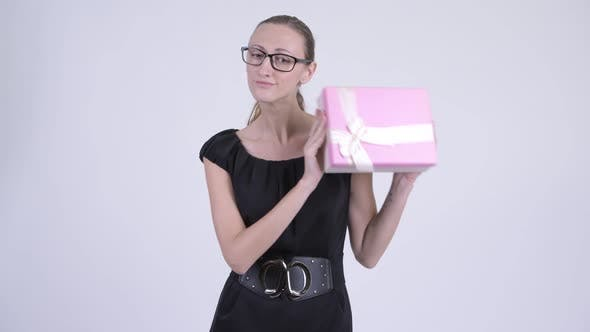 Cover Image for Happy Blonde Businesswoman Thinking While Shaking Gift Box