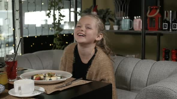 a Little Girl with Blonde Hair Laughs Merrily Sitting in a Restaurant