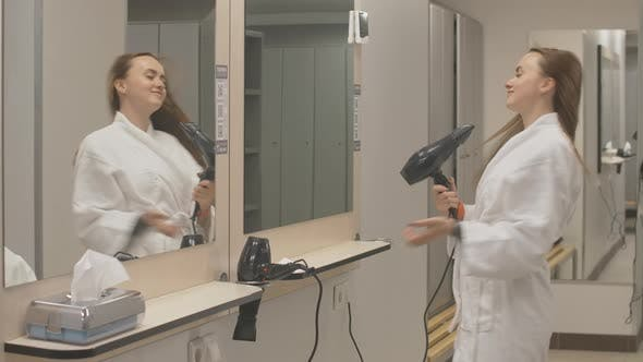 Thumbnail for Young Charming Sportswoman in White Bathrobe Drying Hair with Dryer in Gym Locker Room. Confident