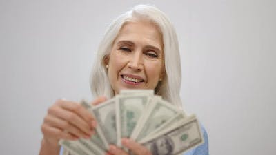 Rich Aged Woman Counting Money in Studio