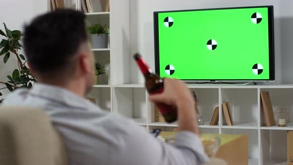 Thumbnail for Man Drinking Beer and Eating Chips while Watching Green Screen TV at Home