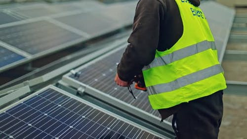Photovoltaic solar energy installation. Solar panel technician installing solar panels