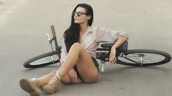 Young Woman Sitting with a Bicycle Outdoor