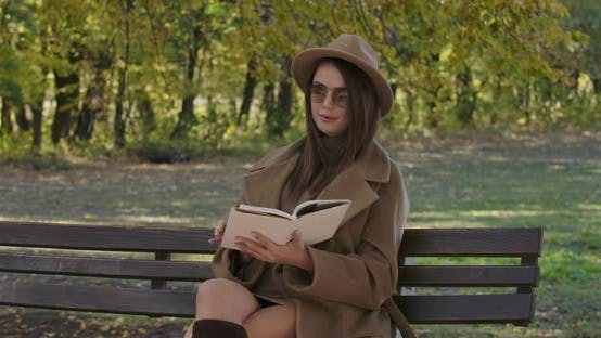 Thumbnail for Smart Elegant Caucasian Woman in Sunglasses and Brown Hat Sitting on Bench and Turning Pages of the
