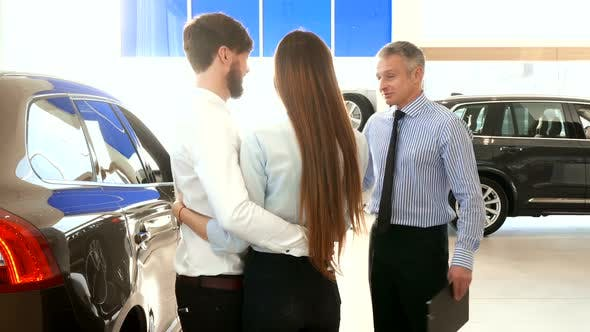 Salesman Consults Young Couple at the Car Dealership