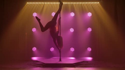Beautiful Pole Dance Performed By an Athletic Young Female. Silhouette of an Attractive Body in a