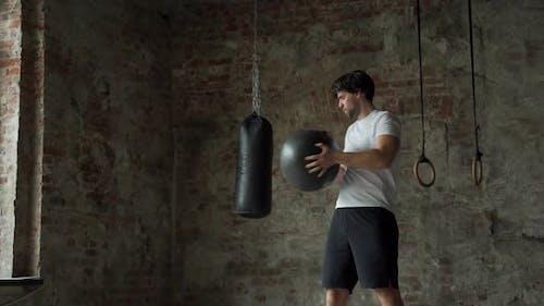 Fitness-Mann macht Übungen für die Presse für Fitness mit Fitnessball im Fitnessstudio