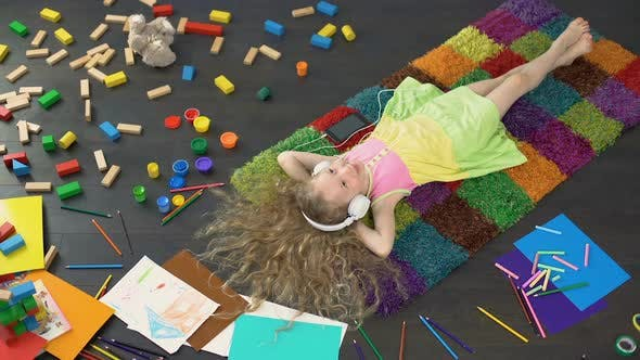 Thumbnail for Cheerful Child Lying on Colorful Carpet and Listening to Music in Headphones