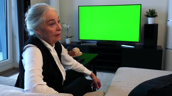 Cover Image for Old Caucasian Woman Watches Television in Living Room and Then Disagrees