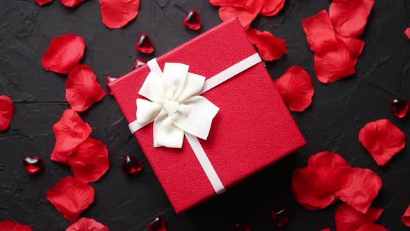 Cover Image for Gift Box on Black Stone Table. Romantic Holiday Background with Rose Petals