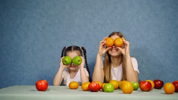 Thumbnail for Girl having fun with mother. Little girl having fun with mother at table with fruits