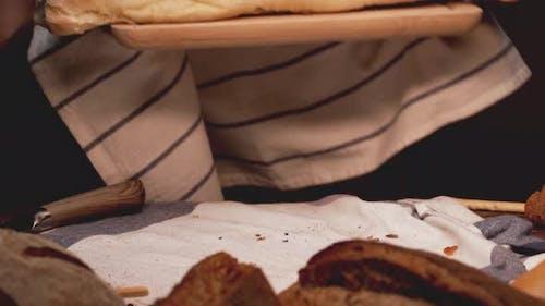 Bäcker legt frisch gemachtes Brot auf den Tisch