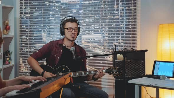 Thumbnail for Recording Hit Song in Home Studio: Young Man in Headphone Singing and Playing Guitar