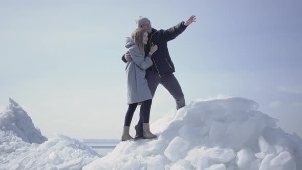 Thumbnail for Beautiful Blond Couple Pointing Away Hugging Each Other