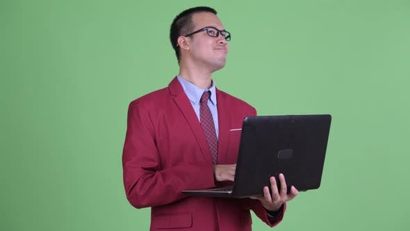 Thumbnail for Happy Asian Businessman Thinking While Using Laptop