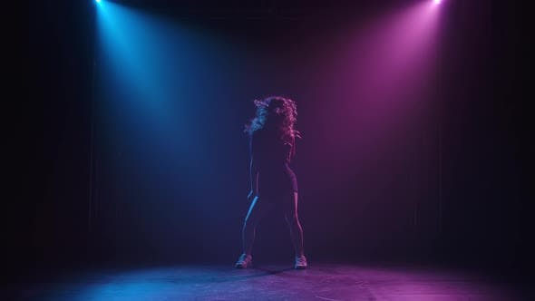 Slim Long Legged Young Female Dancer Practices Jazz Funky Movements in a Dark Studio. Silhouette of