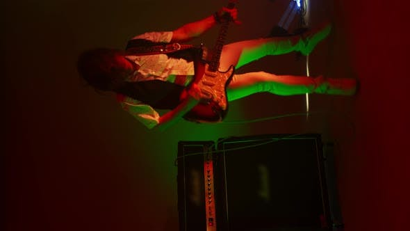 Thumbnail for Vertical Video Crazy Male Rock Musician Playing Guitar in the Studio in the Light of Spotlights and