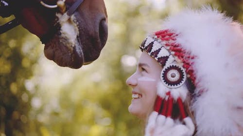 Woman In Headdress Bonding And Smiling With Horse