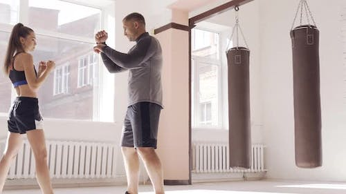 A Young Girl Conducts Kickboxing Training and Practices Hands Strikes with a Professional Boxer