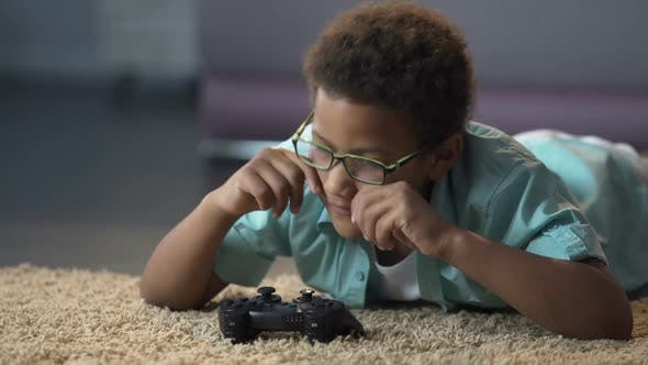 Cover Image for Boys Eyes Tired of Looking at Screen While Playing Video Game, Harm to Health