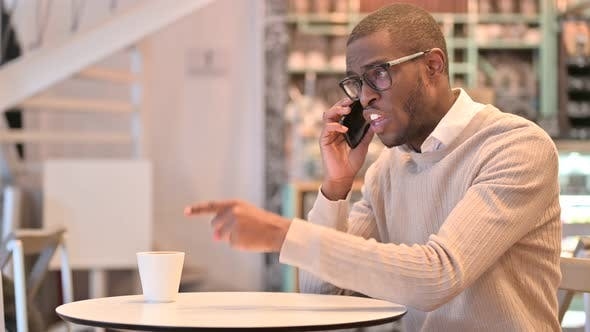 Upset African Man Angry on Smartphone in Cafe