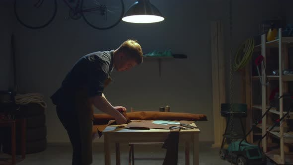 A Craftsman Cuts a Piece of Leather