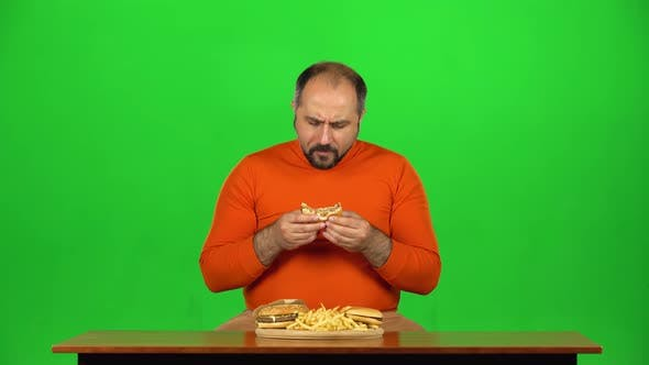 Thumbnail for Funny Adult Man at a Table with a Plate of Fast Food Enjoys Eating a Burger and French Fries, Green