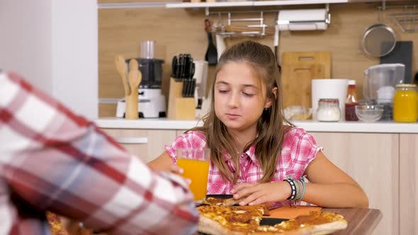 Thumbnail for Young Girl Eating Pizza at the Table