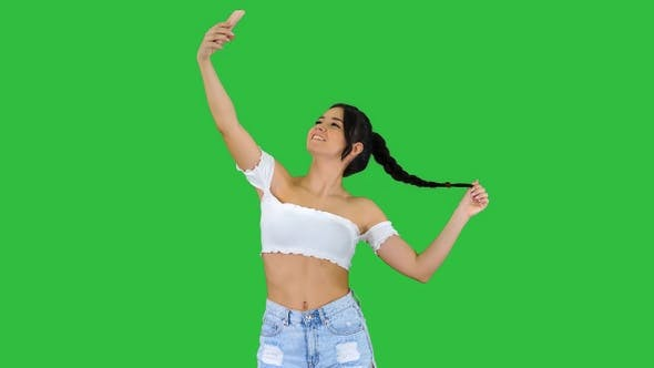 Thumbnail for Cute brunette girl takes a selfie and dancing on a Green