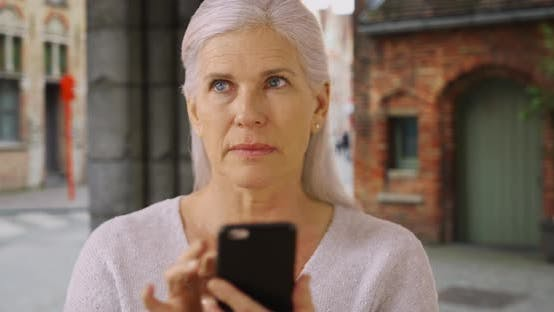 Thumbnail for Worried mature woman tourist lost in Bruges uses app on cellphone for directions