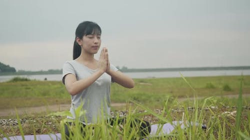 Beautiful Asian female sitting in meditation pose position medicine yoga pranayama balance.