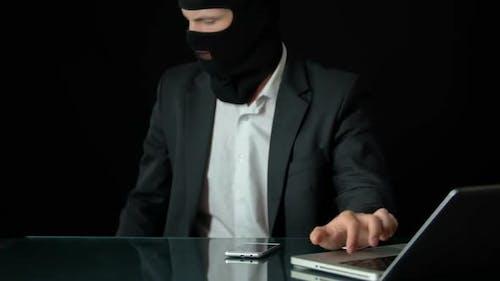 Gun-Man in Balaclava Using Computer, Preparing for Attack, Blackmail Crime