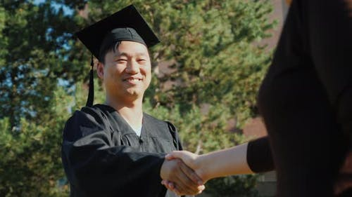 Successful Asian Man in Graduate Clothes Accepts Congratulations
