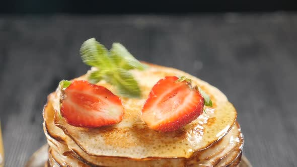 Stack of Pancakes with Fruits and Berries on Top. Hand Puts Mint Leaf on Top. Honey Dripping Down on