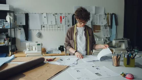 Female Couturier Looking Throuth Sketches Planning New Garments Collection