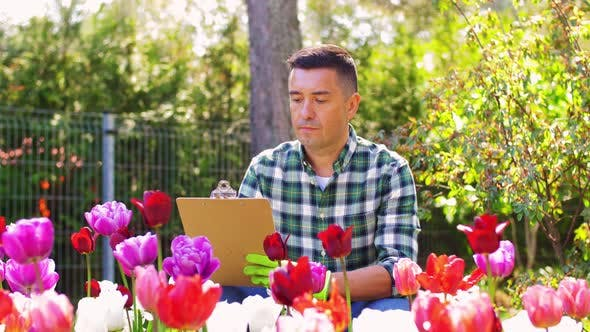 Thumbnail for Man with Clipboard and Flowers at Summer Garden