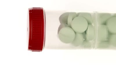Vertical Video Transparent Pills Bottle with Large Green Pills Isolated on White 360 Rotating