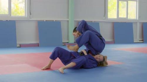 Zwei Kampfsportler Sparring auf dem Boden im Fitnessstudio
