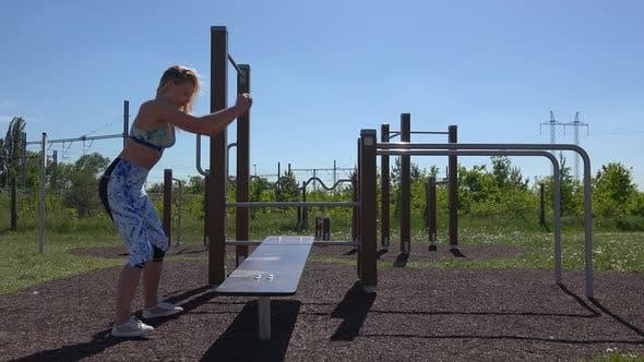 Thumbnail for Eine Passform Schöne Frau springt auf und aus einer Bank in einem Fitnessstudio im Freien.