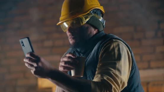 Male Builder with Hot Drink Using Smartphone