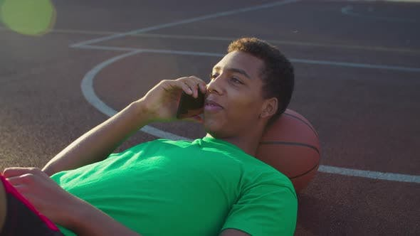 Cover Image for Athlete Chatting on Phone on Basketball Court