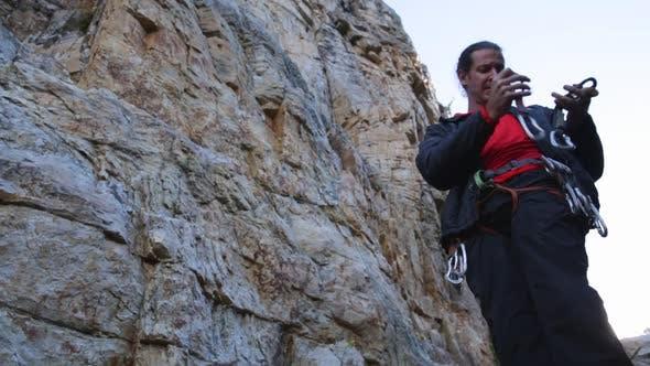 Thumbnail for A young man preparing equipment to go rock climbing.