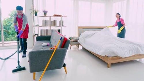 Le mari et la femme nettoient leur chambre ensemble.
