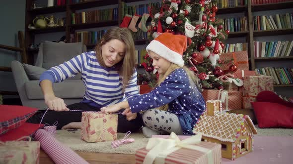 Thumbnail for Mother with daughter wrap Christmas gifts