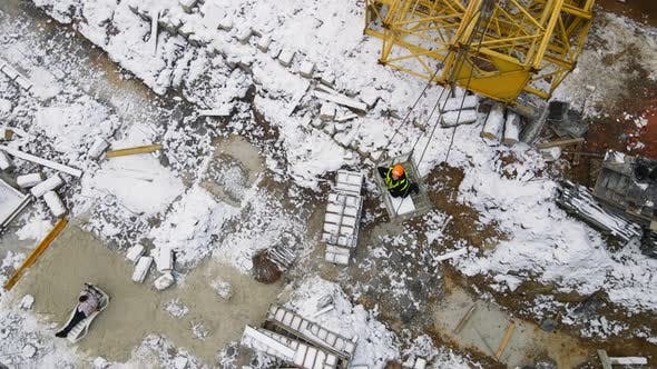 A Woman at a Construction Site Who Was Lifted By a Crane Communicates with a Man Who Is Lying on a