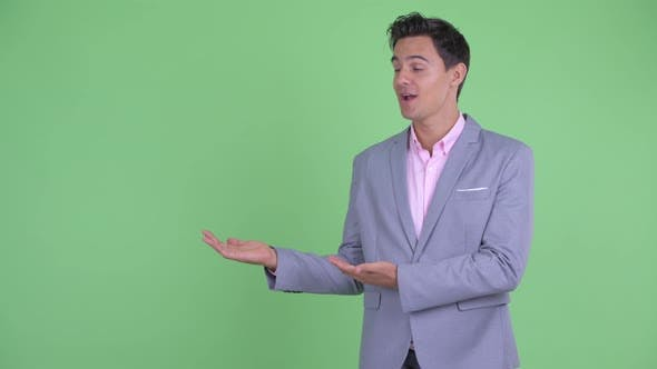 Thumbnail for Happy Young Handsome Businessman Talking and Showing Something