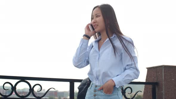 Thumbnail for Pretty Asian Lady Chatting on Phone Outdoor at Summer Day