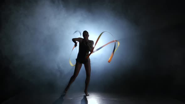 Thumbnail for Gymnast with a Ribbon in the Hands Circling in the Smoke. Black Background. Light Rear. Silhouette