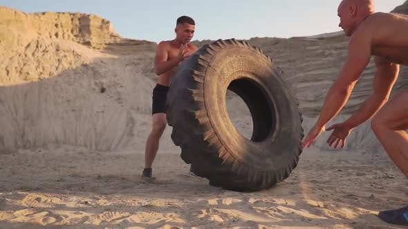 Thumbnail for Two Athletes Train in Active Mode on the Beach Doing push-UPS and Pushing a Huge Wheel